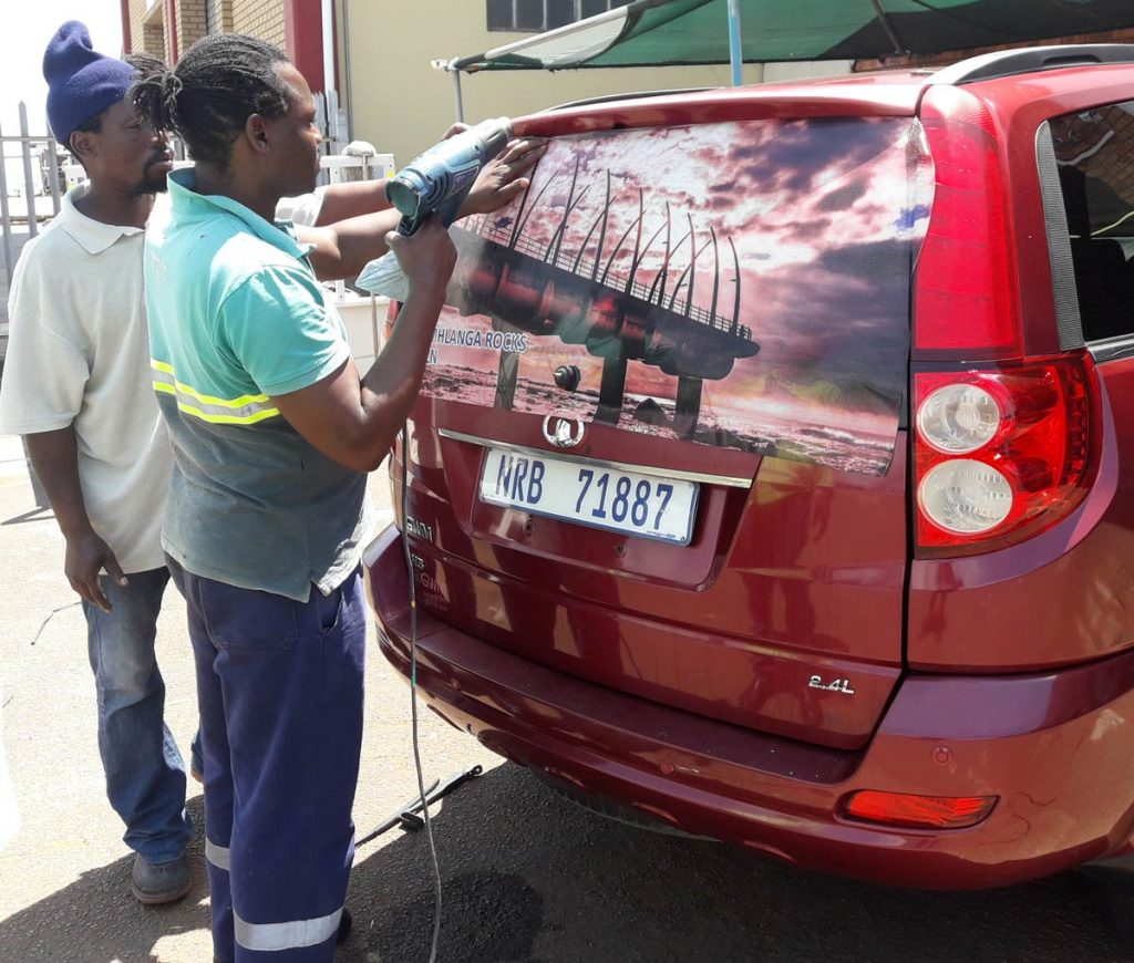 Workers fit a picture of the Umhlanga pier to Jonathan Syster's car before his epic road trip.